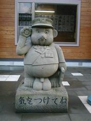 来待駅前に立つタヌキの石像の写真