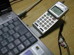 PCカードを装着した611Sをノート型PCに接続した状態の写真